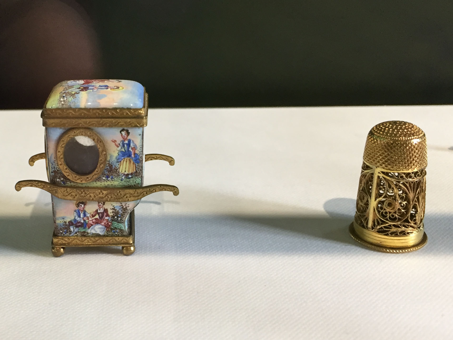 Scatola profumate nella forma di portantina con smalto e montatura in bronzo, Germania, 19° secolo e scatola profumata nella forma di ditale in argento dorato, Inghilterra 19° secolo