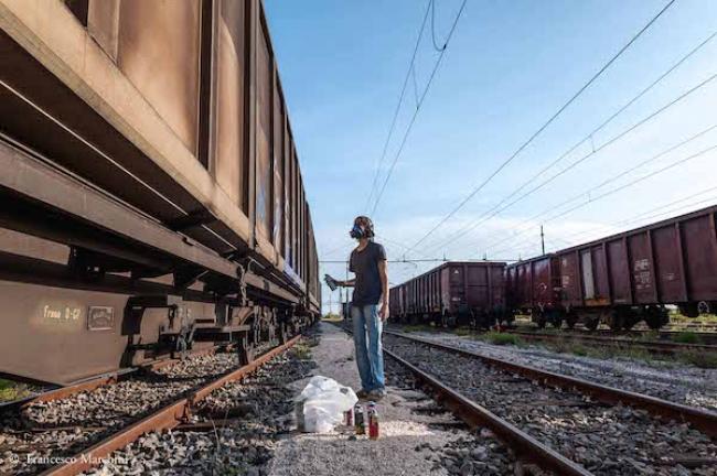 WAOS controlla i colori prima di iniziare a disegnare in un deposito di treni merci abbandonati fuori Roma, 2014
