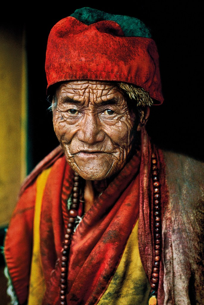 """00340_01, Lhasa, Tibet, 2000, TIBET-10009. Monk at Jokhang temple.  'There was something about his face,' McCurry has said of this monk at the Jokhang temple in Lhasa, Tibet. There was some 'ancient feeling, some kind of ancient truth there. I have never seen a face quite like his.' He looks with intensity into McCurry's camera, deeply aware of the transience of the moment.  """"The lines of time trace a deep personal history across this old monk's face. It seems as though his has been a life of enquiry, a quest for a truth, on a higher level. He looks into the lens of the camera with a searching gaze. That is what attracted McCurry, as he visited the Jokhang Temple on his photographic pilgrimage through Tibet, sketching with his camera the various pathways to the Buddha. - Phaidon 55  Magnum Photos, NYC31836, MCS2000009 K001  Phaidon, 55, Looking East, The Path to Buddha, Iconic Images, final book_iconic, Iconic Photographs  Path To Buddha_Book Steve McCurry_Book Looking East_Book Iconic_Book PORTRAITS_book Untold_book final print_MACRO final print_Sao Paulo final print_Milan final print_Birmingham PORTRAITS_APP final print_HERMITAGE  retouched_Sonny Fabbri 7/13/2015"""